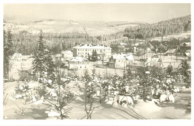 """pohled z Kamlu na Nový svět, již stojí současná škola, tato budova byla otevřena 9.8. 1936. V tom roce se zároveň slavilo 25 výročí založení školy Nový svět v Krkonoších. Do té doby byla škola po několika budovách, například v """"Dobrušce""""."""